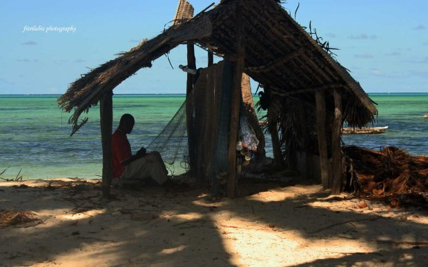 A fisherman fixing his nets in Jambiani Village