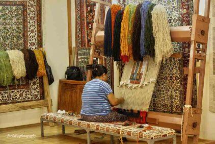 A woman weaving carpet